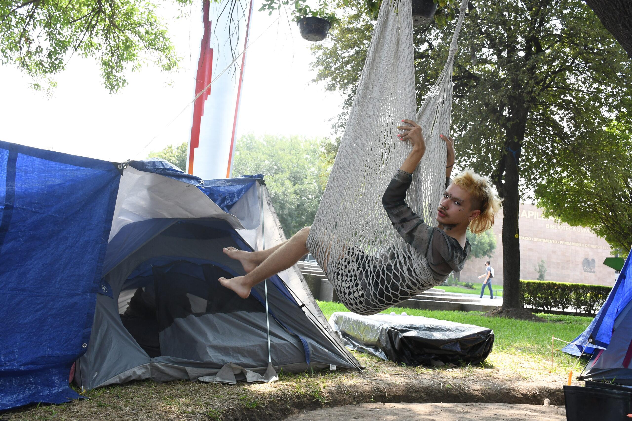 Georgina Agustina se balancea sobre una hamaca, al frente de una casa de campaña azul con blanco. Se ve a Georgina con el cabello medianamente largo, camisa gris, descalce, y con varios piercings en la cara.